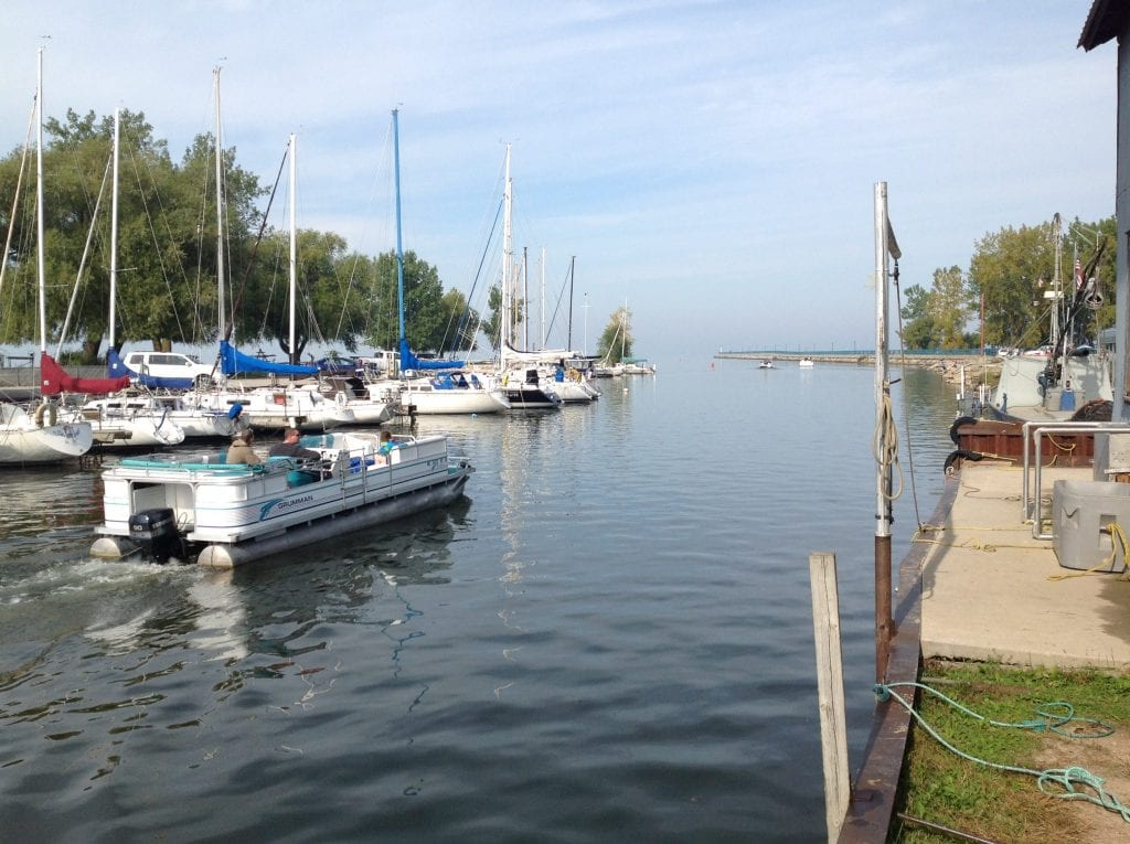 A pontoon boats makes her way out in the late summer - Caseville Harbor in the Fall